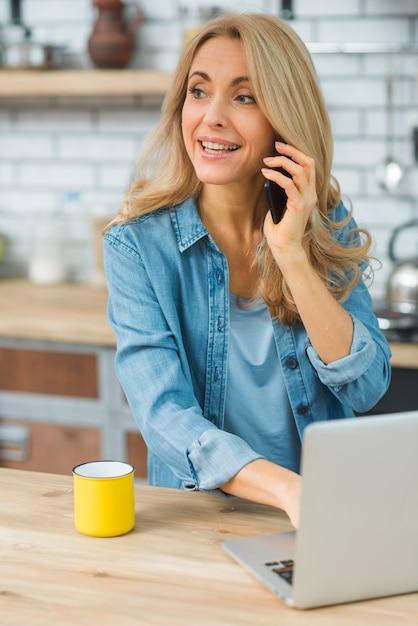 Heureuse jeune femme à l'aide d'un ordinateur portable parlant sur un téléphone intelligent dans la cuisine Photo gratuit