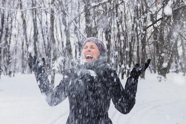 Heureuse jeune femme appréciant les chutes de neige dans la forêt d'hiver Photo gratuit