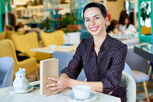 Heureuse Jeune Femme Appréciant Le Temps Dans Le Café Photo Premium