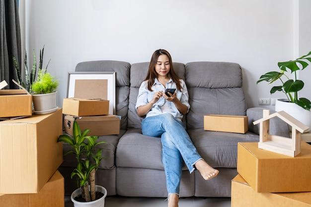 Heureuse Jeune Femme Asiatique à L'aide De Smartphone Avec Pile De Boîtes En Carton Photo Premium