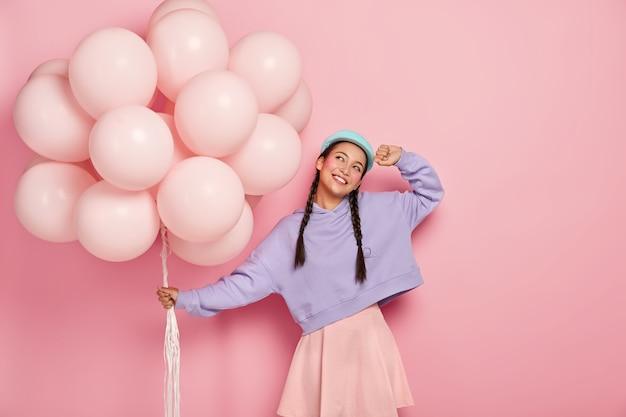Heureuse Jeune Femme Asiatique Avec Deux Nattes, Rêve De Vacances Géniales, Porte Un Bouquet De Ballons à Air, Imagine Un Beau Moment De Célébration, Isolé Sur Un Mur Rose Photo gratuit