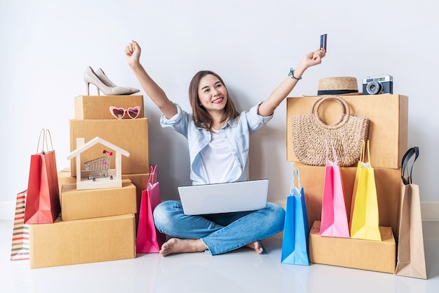 Heureuse Jeune Femme Asiatique Avec Sac à Provisions Coloré Et Pile De Boîtes En Carton à La Maison Photo Premium