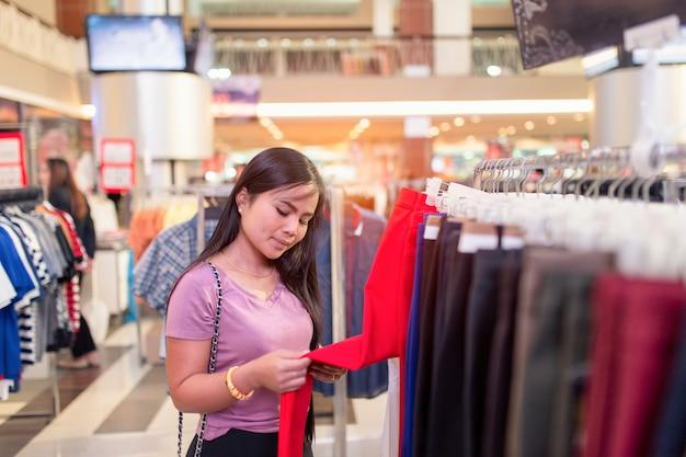 Heureuse jeune femme asiatique vérifiant une étiquette de prix sur un pantalon en centre commercial ou un magasin de vêtements. Photo Premium