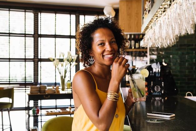 Heureuse jeune femme assise au comptoir tenant un verre de cocktail au restaurant Photo gratuit