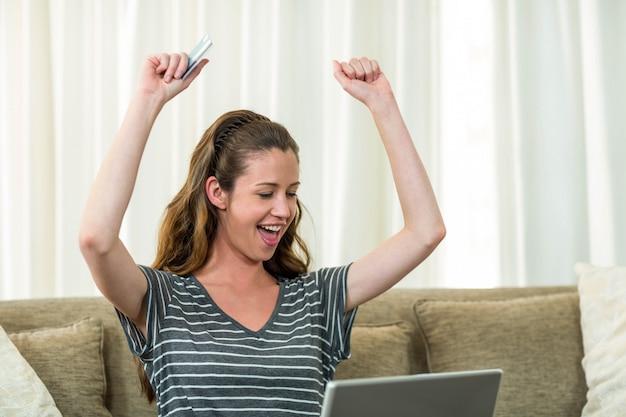 Heureuse jeune femme assise sur un canapé et shopping en ligne avec une carte de crédit Photo Premium