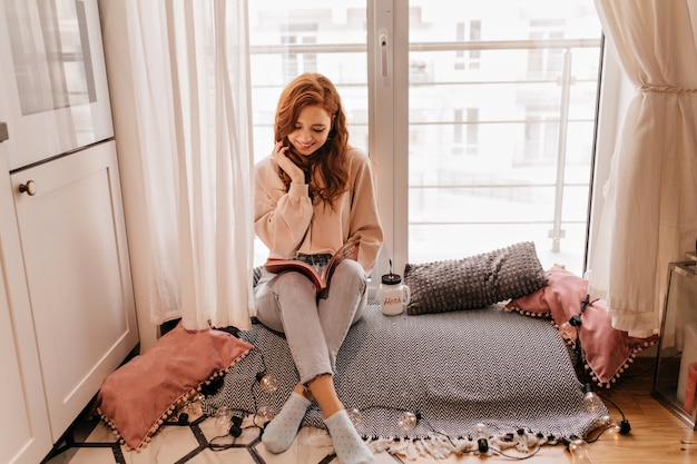 Heureuse Jeune Femme Assise Dans Sa Chambre Douillette. Winsome Fille De Gingembre Posant Avec Livre. Photo gratuit
