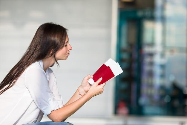 Heureuse jeune femme avec billet d'avion et passeports à l'aéroport en attente de vol Photo Premium