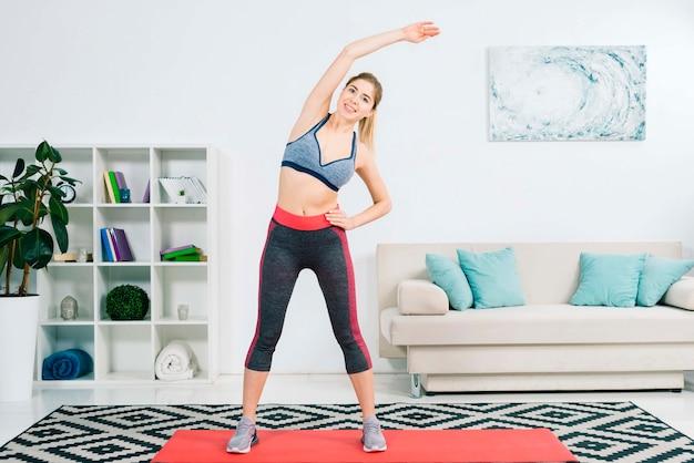 Heureuse jeune femme blonde faisant des exercices d'étirement à la maison Photo gratuit