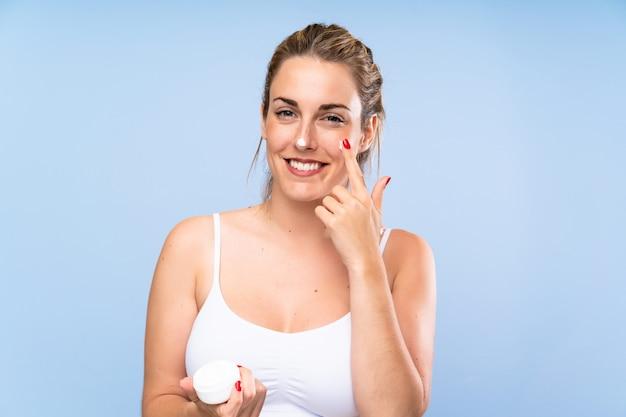Heureuse jeune femme blonde avec un hydratant sur un mur bleu isolé Photo Premium