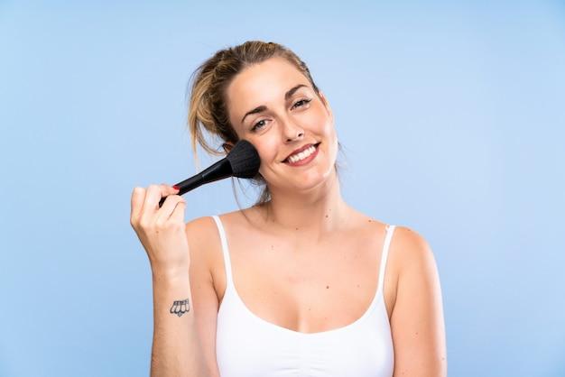 Heureuse jeune femme blonde avec un pinceau de maquillage Photo Premium