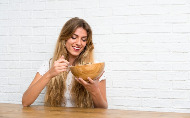 Heureuse jeune femme blonde avec une salade Photo Premium