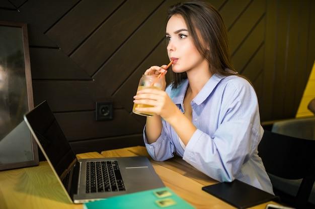 Heureuse Jeune Femme Buvant Une Boisson Fraîche Au Café Avec Ordinateur Portable Photo gratuit