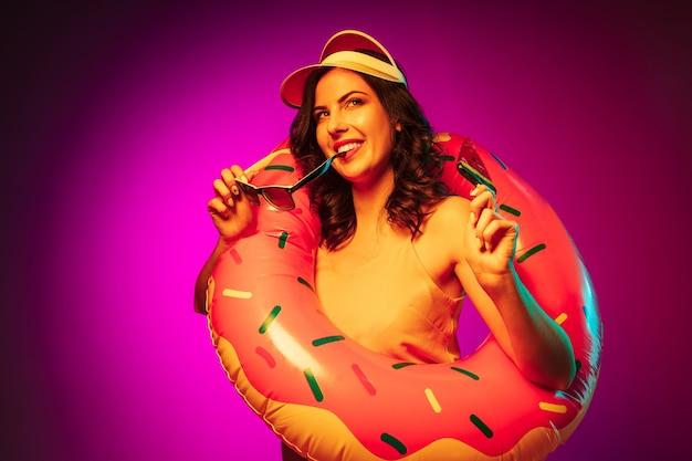 Heureuse Jeune Femme Dans Un Anneau De Plage En Caoutchouc, Bonnet Rouge Et Lunettes De Soleil Avec Un Bonbon Sur Néon Rose à La Mode Photo gratuit
