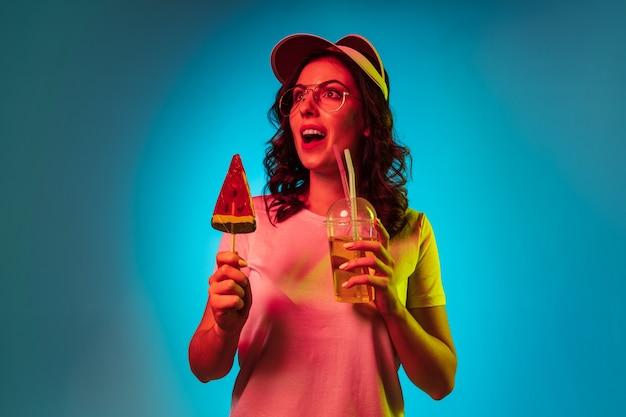 Heureuse Jeune Femme Dans Une Casquette Tenant Des Bonbons Et Des Boissons Sur Studio Néon Bleu Branché Photo gratuit