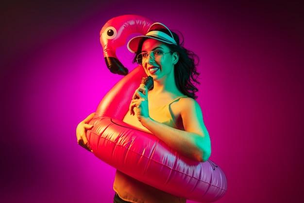 Heureuse Jeune Femme Dans Un Flamant Rose En Caoutchouc, Bonnet Rouge Et Lunettes De Soleil Avec Une Glace Sur Néon Rose à La Mode Photo gratuit