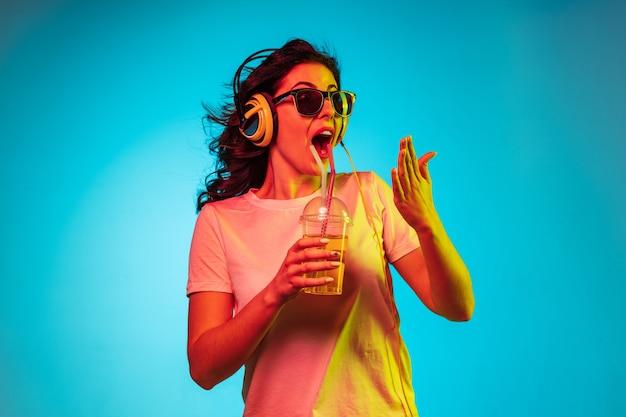 Heureuse Jeune Femme Danse Et Souriant Dans Les écouteurs Sur Studio Néon Bleu Branché Photo gratuit
