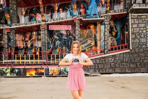 Heureuse jeune femme debout devant la maison hantée au parc d'attractions Photo gratuit
