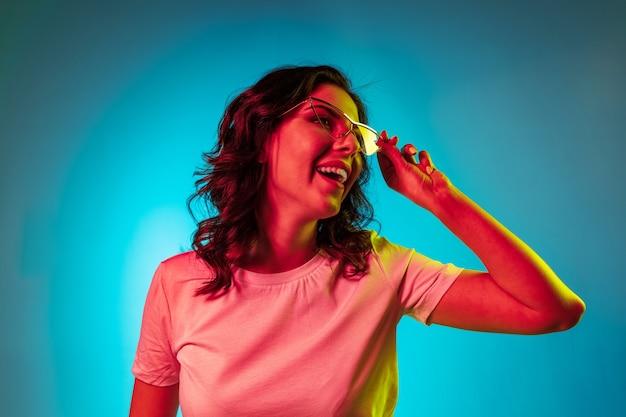 Heureuse Jeune Femme Debout Et Souriant à Lunettes De Soleil Sur Studio Néon Bleu Branché Photo gratuit