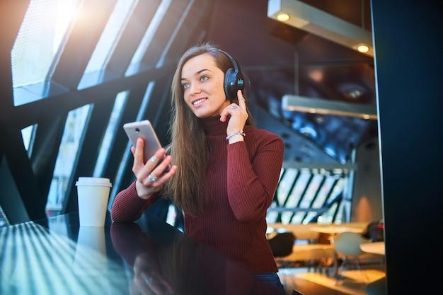 Heureuse Jeune Femme Décontractée Avec Un Casque Sans Fil Noir Et Un Téléphone Appréciant La Musique Dans Un Café. Photo Premium