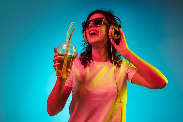 Heureuse Jeune Femme écoutant De La Musique Et Souriant Sur Néon Bleu à La Mode Photo gratuit