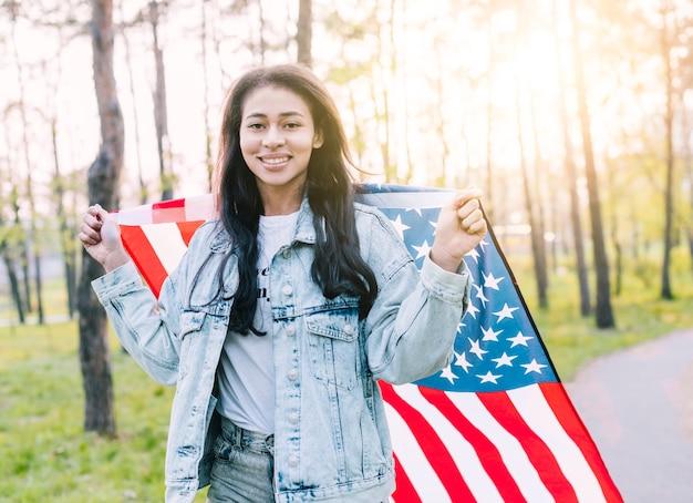 Heureuse jeune femme ethnique avec drapeau américain Photo gratuit