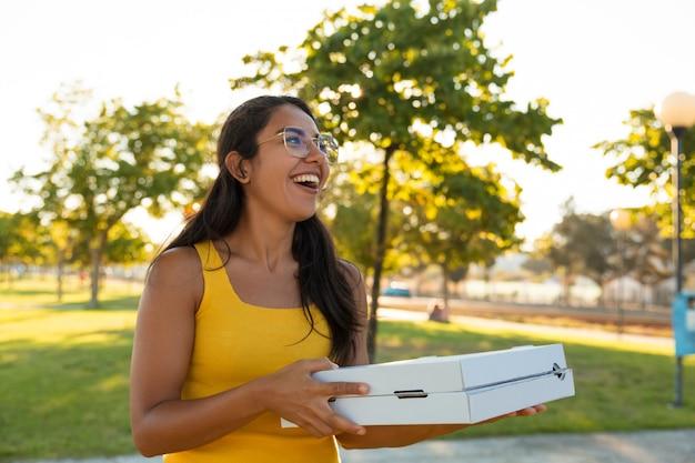 Heureuse Jeune Femme Excitée Transportant De La Pizza Pour Une Fête En Plein Air Photo gratuit