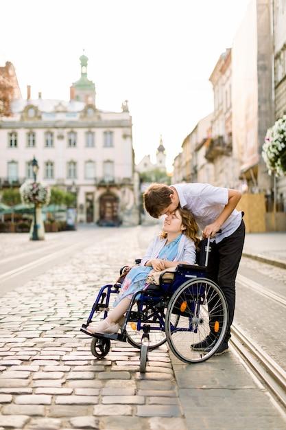 Heureuse Jeune Femme En Fauteuil Roulant Et Son Mari Embrassant Son Front, Marchant à L'extérieur Dans La Vieille Ville Photo Premium