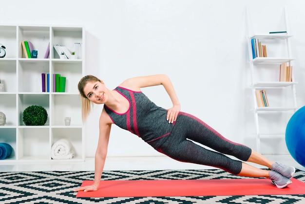 Heureuse jeune femme fitness portant des vêtements de sport faisant des exercices dans le salon Photo gratuit