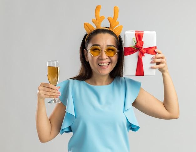 Heureuse Jeune Femme En Haut Bleu Portant Une Jante Drôle Avec Des Cornes De Cerf Et Des Verres Jaunes Tenant Un Verre De Champagne Et Un Cadeau De Noël Souriant Joyeusement Photo gratuit