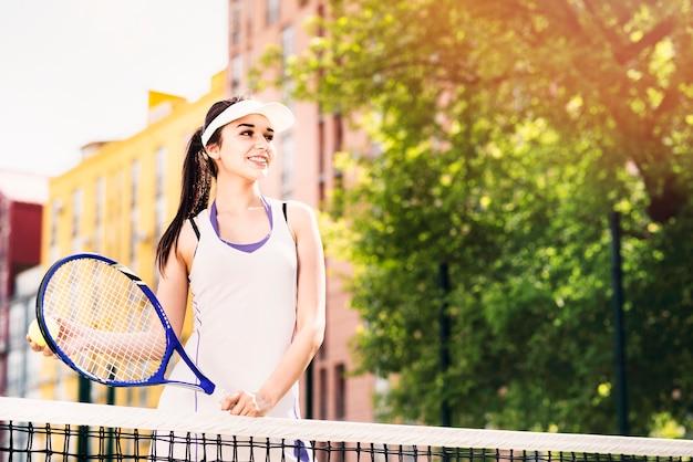 Heureuse jeune femme jouant au tennis sur le court Photo gratuit