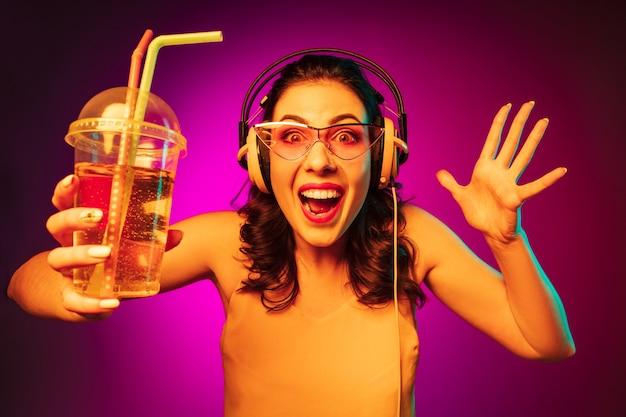 Heureuse Jeune Femme En Lunettes De Soleil Rouges Boire Et écouter De La Musique Sur Néon Rose à La Mode Photo gratuit