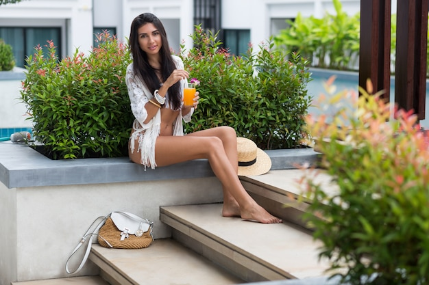 Heureuse Jeune Femme En Maillot De Bain Blanc Boho élégant Assis Près De La Piscine Tropicale Dans Un Hôtel De Luxe Et Profiter D'un Cocktail Ou D'un Jus D'orange. Photo gratuit