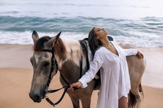 Heureuse jeune femme à la mode dans une robe blanche, posant avec un cheval sur la plage. Photo Premium