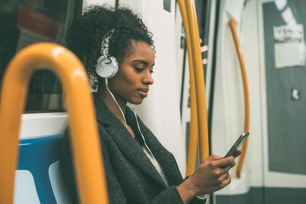 Heureuse jeune femme noire assise dans le métro en écoutant de la musique Photo Premium