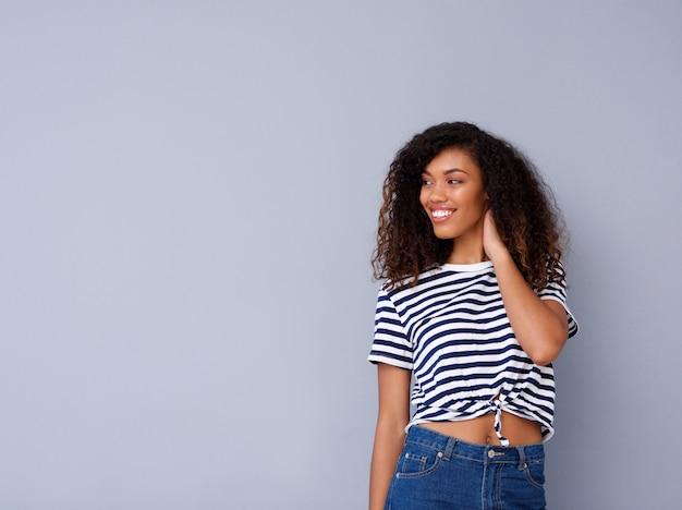 Heureuse jeune femme noire souriant en chemise rayée sur fond gris Photo Premium