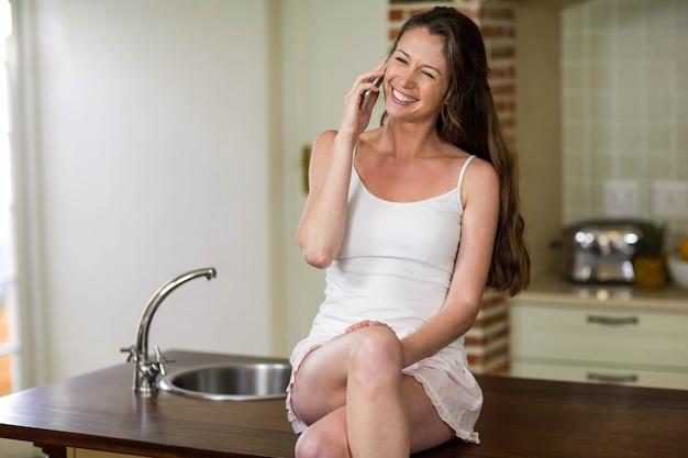 Heureuse jeune femme parlant au téléphone portable dans la cuisine Photo Premium