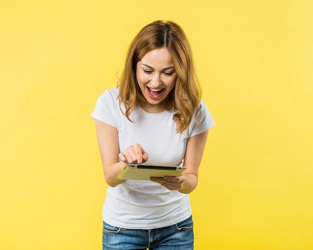 Heureuse jeune femme pointant du doigt sur une tablette numérique sur fond jaune Photo gratuit