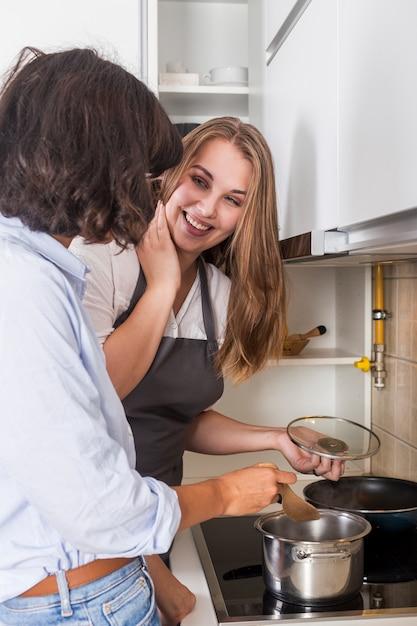 Heureuse jeune femme préparant la nourriture dans la cuisine Photo gratuit