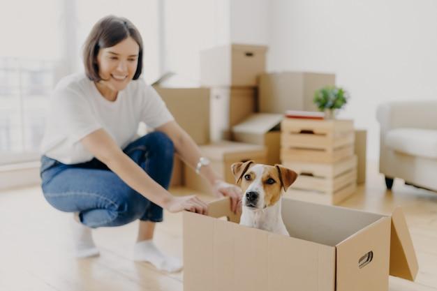 Heureuse jeune femme propriétaire d'une maison pose près d'une boîte en carton avec son animal préféré Photo Premium