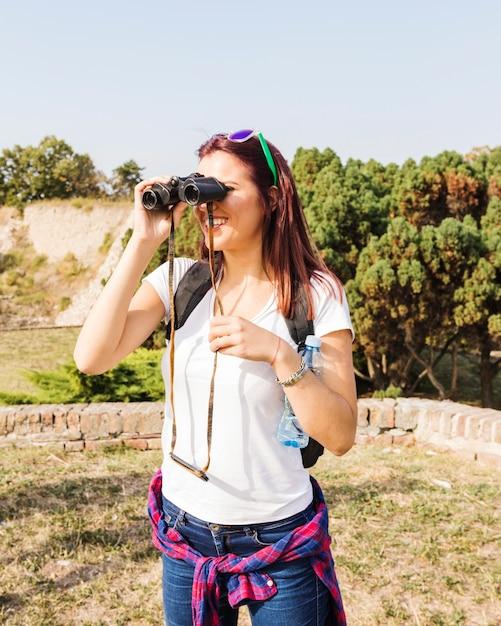 Heureuse jeune femme regardant à travers des jumelles à l'extérieur Photo gratuit