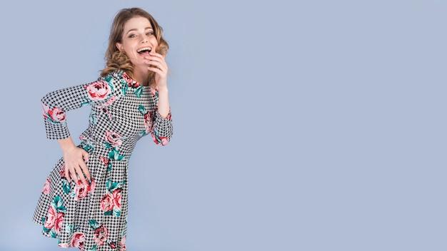 Heureuse jeune femme en robe élégante avec la main sur la hanche Photo gratuit