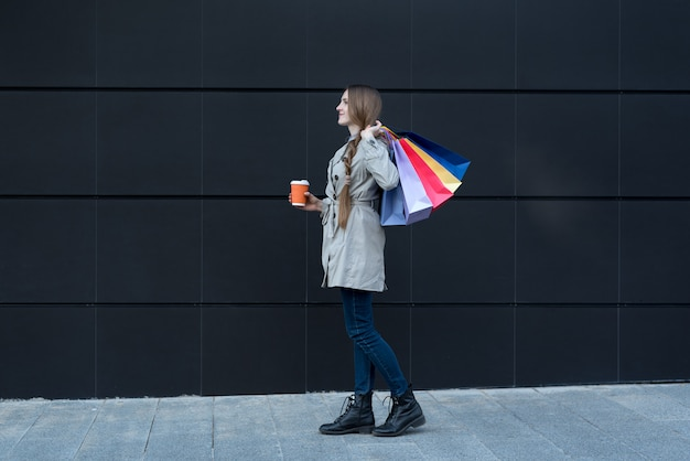 Heureuse jeune femme avec des sacs colorés et gobelet en papier. Photo Premium