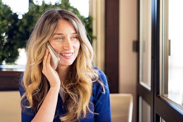 Heureuse Jeune Femme Souriante Tout En Parlant Au Téléphone Photo Premium
