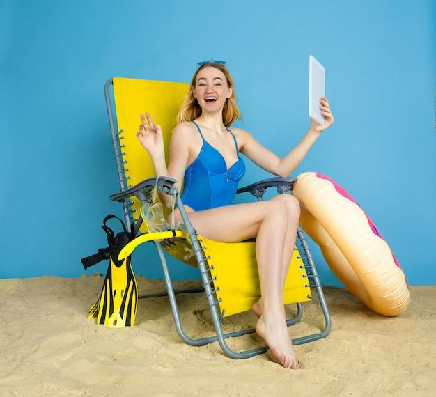 Heureuse Jeune Femme Avec Tablette Prend Selfie Ou Vlog Sur Les Voyages Sur L'espace Bleu Photo gratuit
