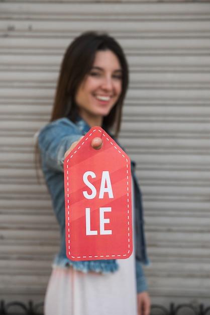 Heureuse jeune femme avec tablette près du mur profilé Photo gratuit