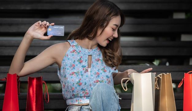 Heureuse Jeune Femme Tenant Une Carte De Crédit Avec Des Sacs à Provisions, Dépenser De L'argent Avec Profiter De Faire Du Shopping. Photo Premium