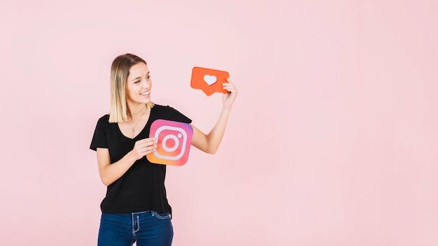 Heureuse jeune femme tenant l'icône de l'amour et instagram Photo gratuit