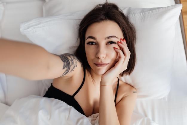 Heureuse Jeune Femme Tenir Un Téléphone Intelligent Couché éveillé Dans Son Lit Le Matin Faisant Vue De Dessus Selfie Photo gratuit