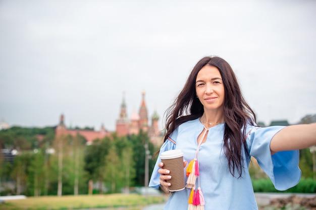 Heureuse jeune femme urbaine, boire du café dans la ville européenne. Photo Premium