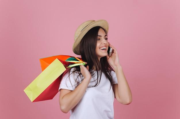 Heureuse jeune femme utilise son téléphone posant avec des sacs à provisions colorés dans le studio Photo gratuit